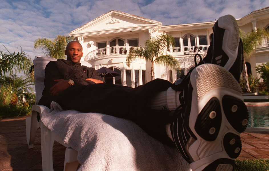 LA Lakers rookie, Kobe Bryant, kicks back in front of the house he purchased for he and his parents in Pacific Palisades, California. Bryant was the first guard to ever be taken out of high school. Since he was still 17 at the time of the draft, his parents had to cosign his contract with the Lakers until he was able to sign his own when he turned 18 before the season began.