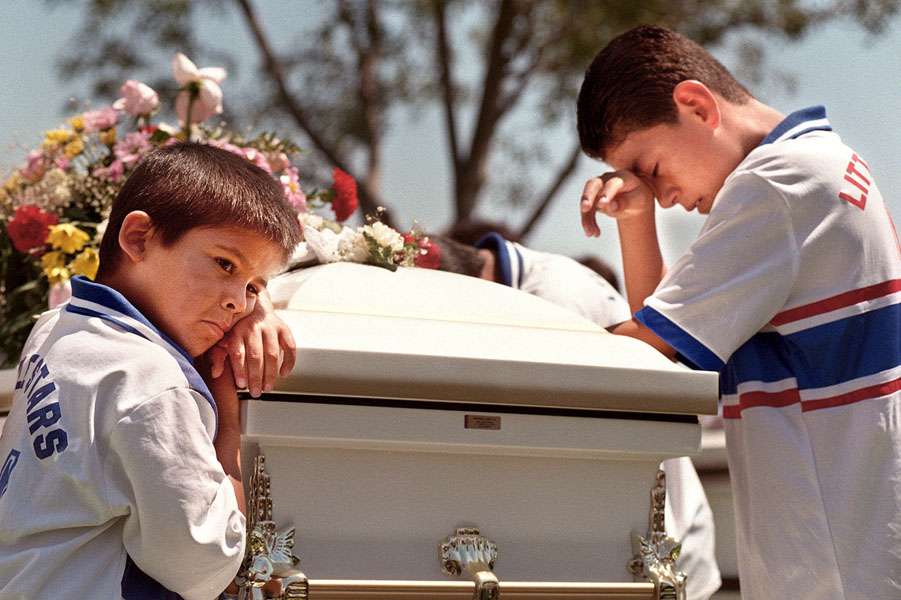 David Castillo, 7, (on left) and Salvador Alcaraz, 12, express their sorrow for the loss of fellow soccer team member Carlos Jr., 8 during the burial of Carlos Granandos Gallardo, 27, Magdalena Lopez, 25, and their four children: Carlos, 8,; Adriana, 4;Jesus, 2, and Jose, 1. The six family members were killed instantly when a pick up truck, operated by a drunk driver, plowed into their parked car.