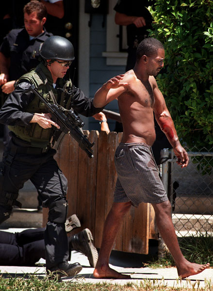 The S.W.A.T. team quicks escorts a victim from an apartment building during a standoff between a gunman and police in Long Beach. The victim had been shot in the left arm and buttocks and taken to St. Mary Medical Center. The standoff began when another man fired at Police.