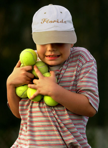 Philip Seeger, 7, works to carry as many tennis balls as he can during the GrassRoots Tennis Camp at the St. Petersburg Tennis Center.