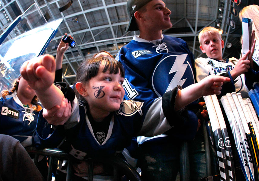 """Tampa Bay Lightning fan Isabella, 4, who goes by the name """"Izzy"""", sticks her arms out waiting to get a fist bump from the Lightning players before they walk down the tunnel as they head out onto the ice for the pre game warm up on opening night against the Florida Panthers at the St.Pete Times Forum in Tampa."""