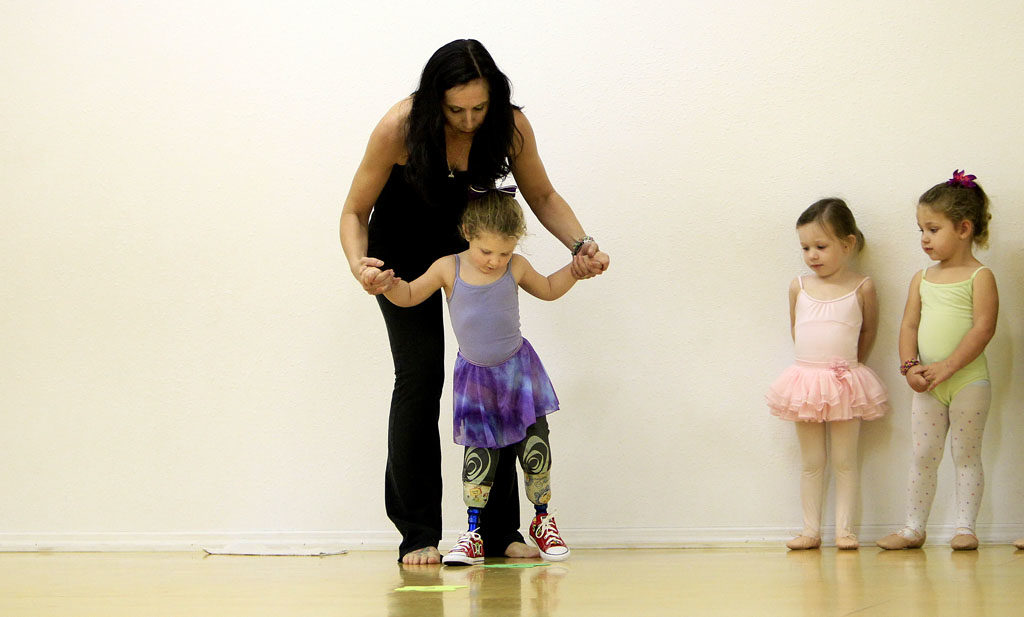 DIRK SHADD   |   Times   Ireland Nugent, 3, gets some help from dance instructor Tonya Guldenpfennig during a ballet class at Premier Dance Academy in Clearwater (12/11/13). Nugent wears prosthetic legs after she lost her lower legs and feet in a lawn mower accident.