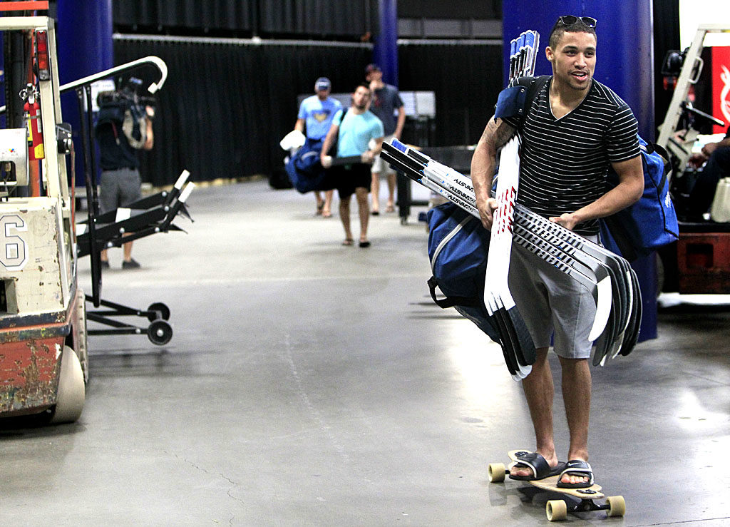 DIRK SHADD   |   Times   Tampa Bay Lightning right wing J.T. Brown rides his long board while carrying his sticks and gear as he exits the Times Forum after players did exit interviews with the coaching staff as their season ends at the Tampa Bay Times Forum in Tampa Thursday (04/24/14).