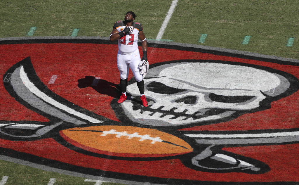 DIRK SHADD   |   Times Tampa Bay Buccaneers defensive tackle Gerald McCoy (93) after taking a knee in prayer at the logo not he 50 yard line before the game starts. Bucs vs Rams home opener at Raymond James Stadium in Tampa Sunday afternoon (09/25/16).