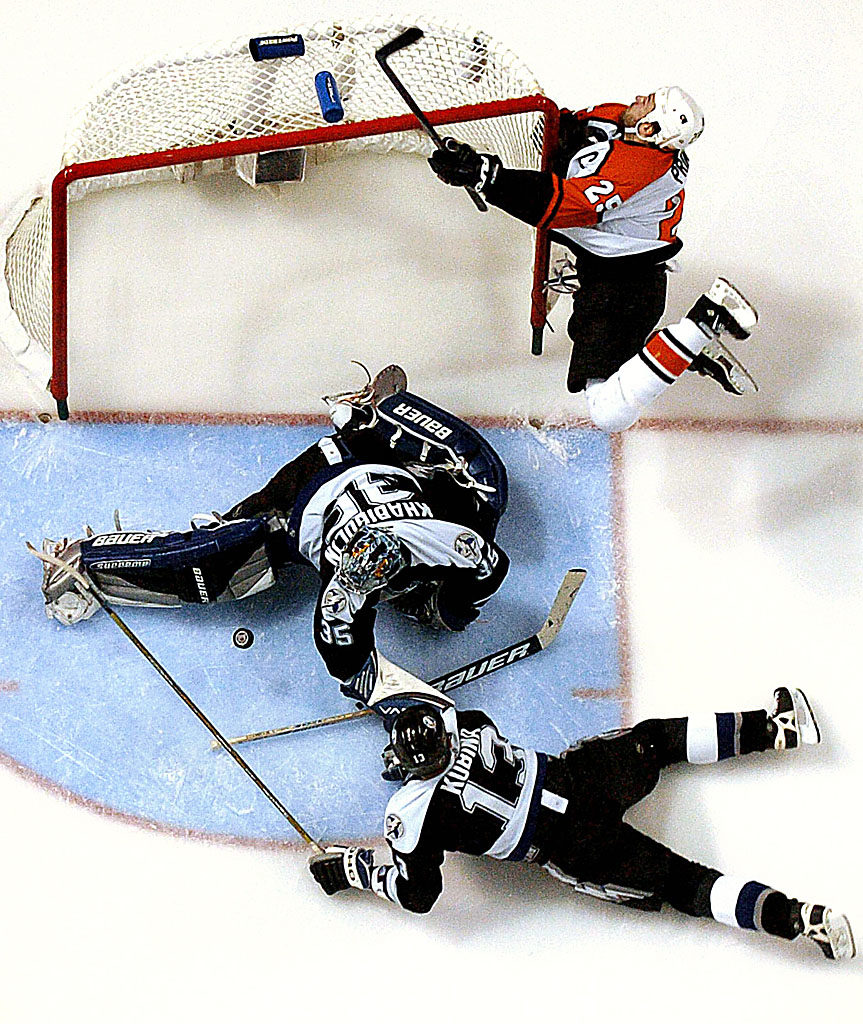 Philadelphia Flyers captain Keith Primeau crashes into the goal while trying to score as Lightning goaltender Nikolai Khabibulin makes the save with Pavel Kubina sprawling to help in the second period of game 7 of the Eastern Conference Finals at the St. Pete Times Forum in Tampa.