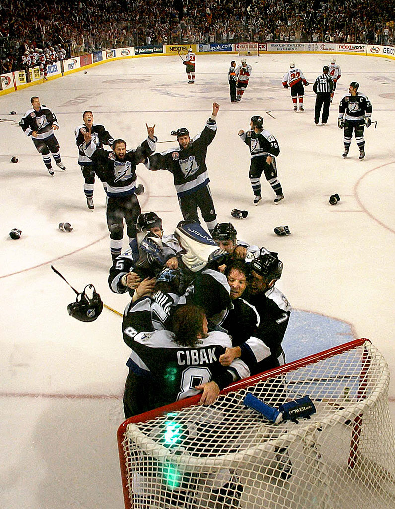 Tampa Bay Lightning players rush onto the ice to congratulate goalie Nikolai Khabibulin as the horn sounds ending game 7 as the Lightning defeat the Calgary Flames to win the Stanley Cup.