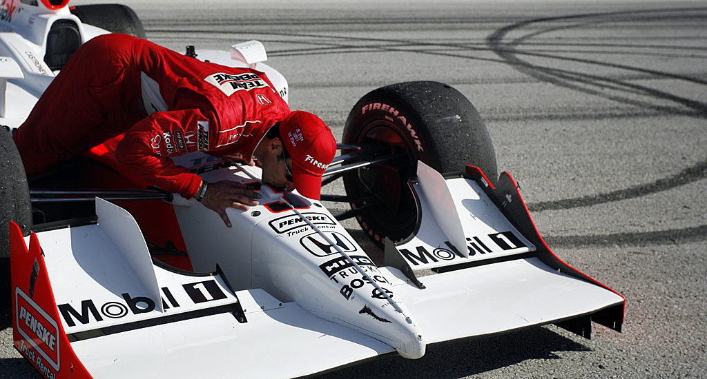 Helio Castroneves kisses his car after doing donuts as he celebrates winning the Honda Grand Prix of St. Petersburg.