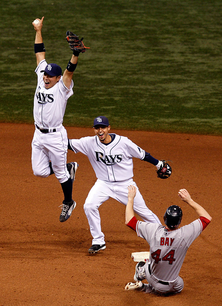 Tampa Bay Rays Akinori Iwamura jumps in the air after stepping on second base beating Red Sox Jason Bay to get the last out as the Rays defeat the Red Sox during game seven of ALCS playoff action at Tropicana Field in St. Petersburg. With this win the Rays moved on to their first World Series appearance.