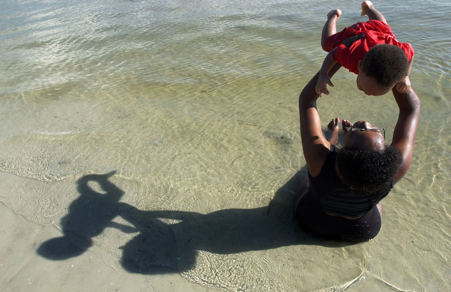 """SP 129359 - - DELIVER TO: METRO - - 9/30/2001 - - ST. PETE - - CAPTION INFO: *** -1/1- Tara Oquendo (cq) plays with her 10-month-old son Juan Oquendo (cq) while sitting in the shallow waters of Gandy beach off of Gandy Blvd. in St. Petersburg Sunday afternoon (9/30/01). """"It's nice and pleasant,"""" Tara Oquendo said. Oquendo, from Lakeland, visits Gandy beach about once a month. - - Times Photo By: Dirk Shadd - - Story By: none - - SCANNED BY: dirk - - RUN DATE: 10/1/2001"""