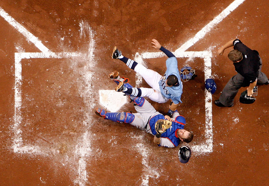 Tampa Bay Rays Sean Rodriguez drops his shoulder and runs over Texas Rangers catcher Mike Napoli to score on a double by Matt Joyce with home plate umpire Greg Gibson there to make the call during second inning action of game four of the American League Division Series at Tropicana Field in St. Petersburg.