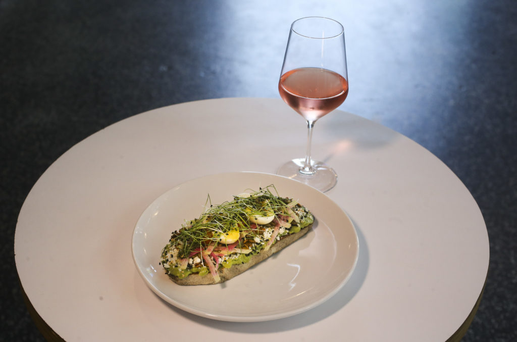 The Avocado Toast and a glass of wine at Bandit Coffee, 2662 Central Ave, on Friday, Aug. 9, 2019 in St. Petersburg. Bandit Coffee is one of the coffee shops that have expanded to serve food in addition to beer and wine. The Avocado Toast features sourdough toast, guacamole, cotija cheese, dehydrated tomatoes, chimichurri, radish, seed blend and micro greens. . DIRK SHADD   |   Times