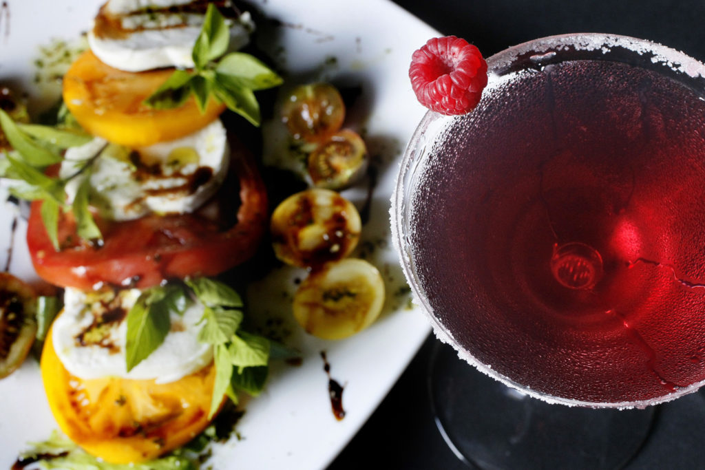 "DIRK SHADD   |   Times   Alma at 111 Boardwalk Place, 2nd floor, in John's Pass Village on Madeira Beach (09/25/14). Pictured is the Tomatoes and fresh mozzarella with basil, olive oil, and aged balsamic vinegar. The drink is a blackberry, raspberry and sage infused tanqueray gin martini. Café Alma, one of downtown St. Petersburg's anchor restaurants for the past 12 years, closed this summer and reopened promptly as the briefer ""Alma"" at 111 Boardwalk Place at John's Pass in Madeira Beach. The menu at the much larger, 300-seat Alma echos that of the cafe, but with more of a focus on Florida foods, from Seminole tribe beef to fish right off the John's Pass dock. There is a dinner-only tablecloth side and a ""come as you are"" flip-flop-friendly side."