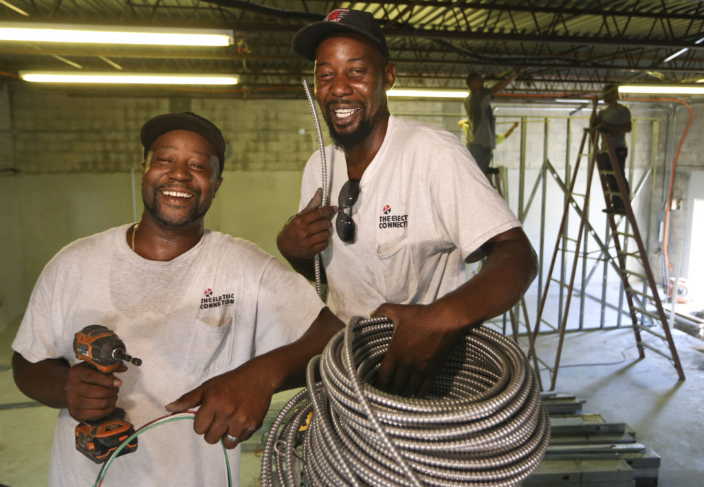 """Clifton """"CJ"""" Graham Jr., 39, on left, and his brother Tavaris Graham, 37, electricians with The Electric Connection Inc. while on the scene of a commercial job at Bass Underwriters, 3227 Bennett St., on Monday, July 29, 2019 in St. Petersburg. The brothers are second generation electricians as their dad, Clifton Graham Sr. is also an electrician.""""My dad got me into it when I was young and it's something I feel in love with,"""" CJ said about being an electrician. """"I love everything about it. I love trouble shooting, I love working inside switch gear and panels."""" Tavaris added, """"It's a family thing. That's how we got into it, from dad."""" CJ said, """"He's very proud of us. He tells us all the time."""" DIRK SHADD   