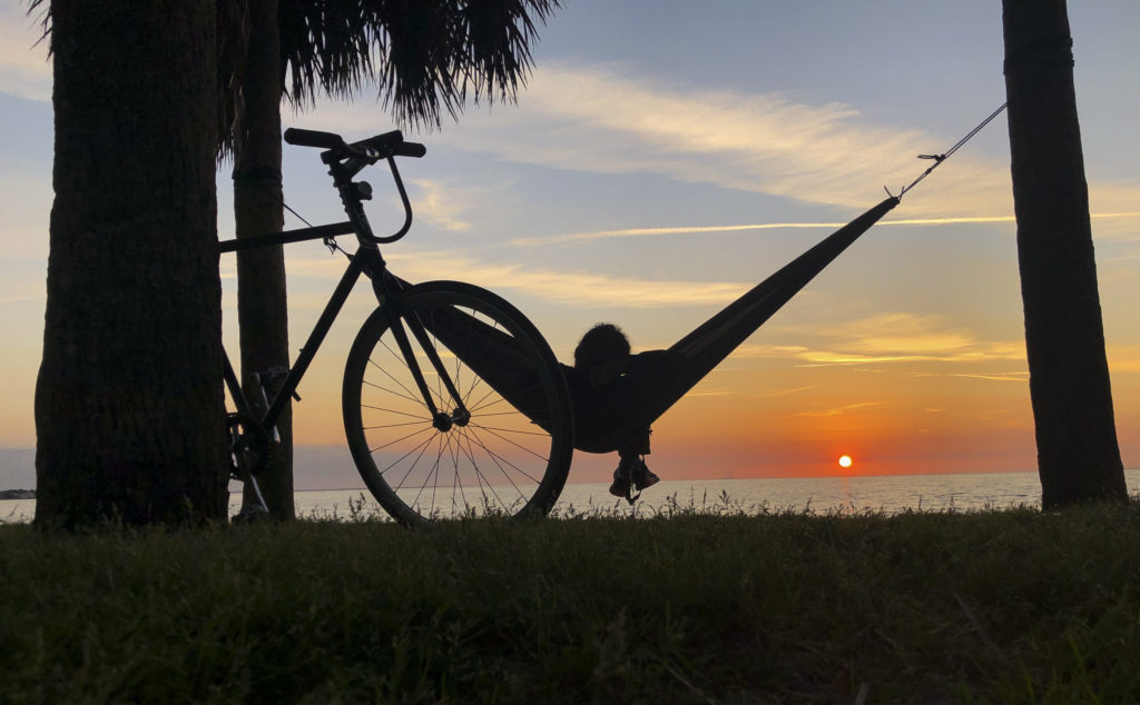 "Aaron Murray, 45, from St Petersburg, relaxes in his hammock as he watches the sunrise over the water at North Shore Park on Monday, March 16, 2020 in St. Petersburg. ""I try to chase as many as I can, Murray said about watching the sunrise. ""It really helps set the tone for the day."""