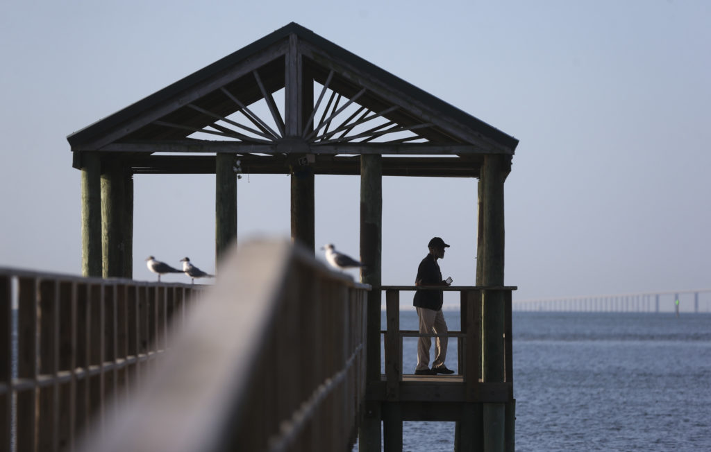 """Basil Roberts enjoys relaxes while talking on the phone on the gazebo at Bay Vista Park 7000 4th St S, on Tuesday, March 17, 2020 in St. Petersburg. """"You can feel the Corona effect on the people,"""" Roberts said. """"Everyday is like a Sunday. The roads are empty, there are no schools."""""""